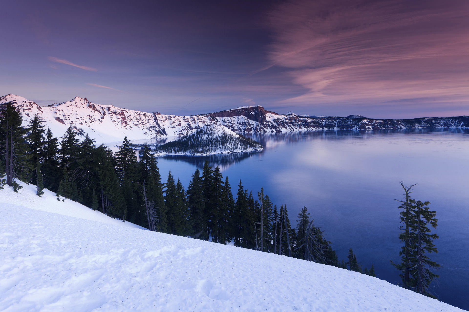 Snow capped mountains surround Crater Lake