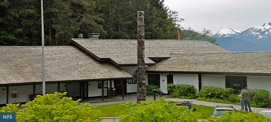 The Sitka National Historical Park Visitor Center is a single story, L-shaped building with a large, low pitch roof, white walls, and brown trim with a tall totem pole standing in front of the building and evergreens along the back
