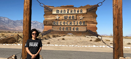 Kim Hirose stands in front of a wood sign suspended from two wood poles that says Manzanar War Relocation Center, desert land and mountains can be seen in the distance
