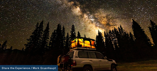 An SUV is parked with an illuminated pop-up tent set up on its roof, the starry sky lights the sky and tall silhouettes of evergreen trees line the horizon