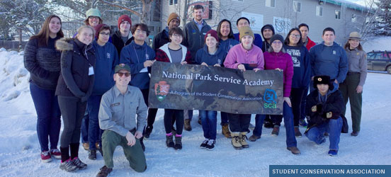 group of park professionals standing in the snow holding a NPS Academy banner