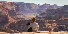 young woman sits with her dog overlooking the Grand Canyon