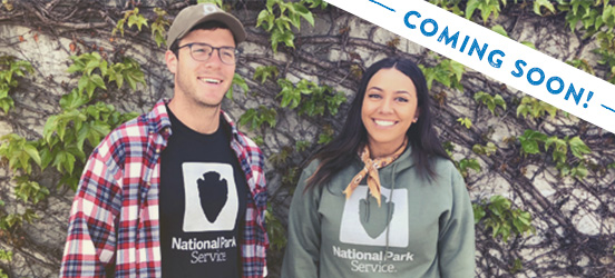 young man and woman stand in front of an ivy-covered wall wearing National Park Service apparel