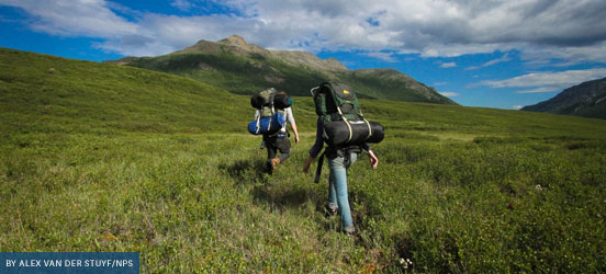 Two hikers with backpacks walking through a grassy field towards a hilltop