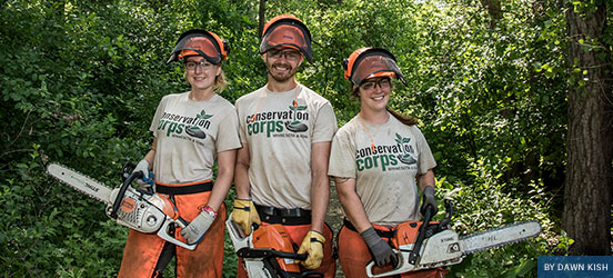 Three members of the Conservation corps pose with chain saws while working in the forest
