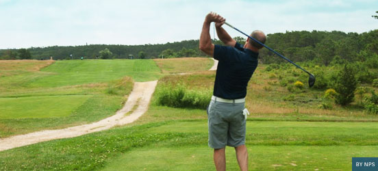 A man swings a golf club on a golf course on Cape Cod National Seashore