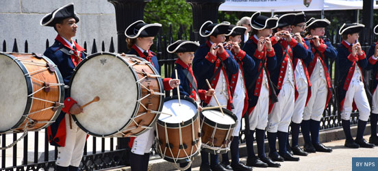 line of young men dressed as revolutionary war era attire, playing fifes and drums in a line