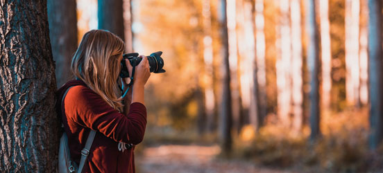 young woman takes a photo in the woods while leaning against a tree