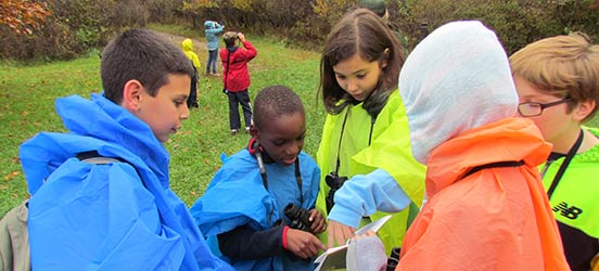 a group of students huddle around a book while exploring Cuyahoga Valley National Park