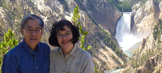 Petta and Ron Khouw pose in front of a waterfall in Yellowstone National Park