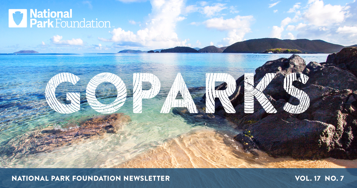 National Park Foundation, GoParks newsletter graphic cover image of a beach with clear blue water and mountainous islands dotting the horizon at Virgin Islands National Park