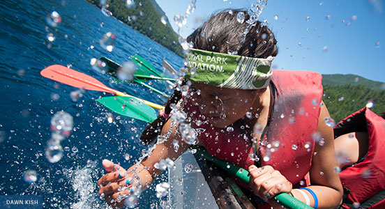 young woman splashes water into her face while paddling in Crescent Lake in Olympic National Park. Photo by Dawn Kish.