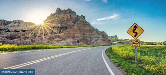 winding road in front of a rock formation in badlands national park, image photographed by Jason Mrachina (Flickr)