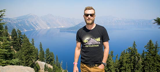 country musician Dierks Bentley posing in front of green trees over Crater Lake National Park