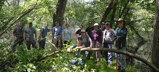 A group on people pose among trees while working at Concord National Wild and Scenic Rivers