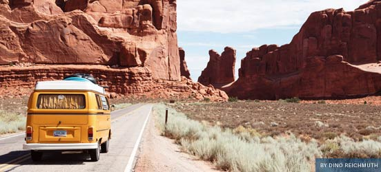 yellow van driving down the road through the desert on a sunny day
