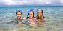 group of girls swim in the ocean and smile at the camera