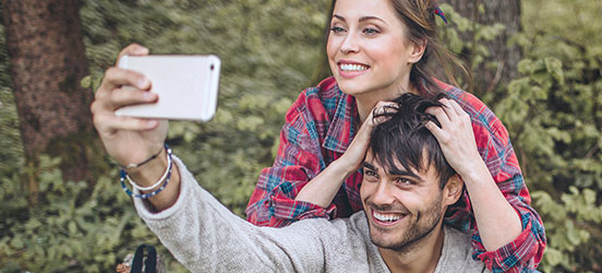 A young couple poses with each other to take a selfie amongst a forest of trees