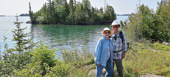 Charlene and Gerry Keller posing together at the edge of the water