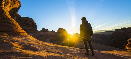 Young man stands and watches sunrise in Arches National Park