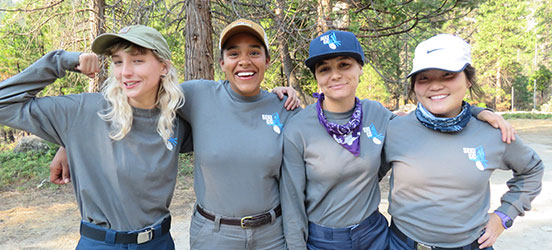 group of four female trail crew members pose together in Sequoia & Kings Canyon National Park