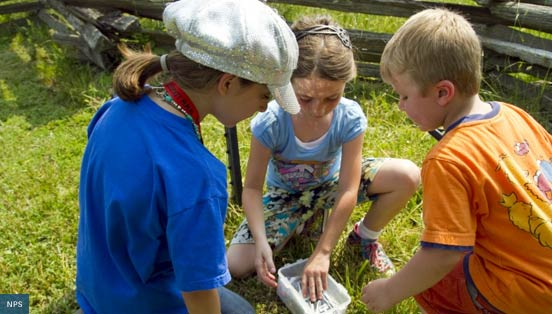 three young kids gather to geocache at Captain John Smith Chesapeake National Historic Trail