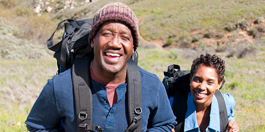 An African American man and woman hiking in the grass with backpacks and smiling at the camera