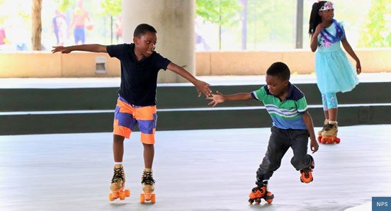 two young boys roller skating on a rink in Anacostia National Park