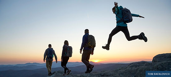 four people hiking on a mountain trail while watchign the sunset. One person leaping into the air.