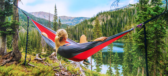 Young woman sits in a red hammock overloking a lake and mountains surrounded by green trees
