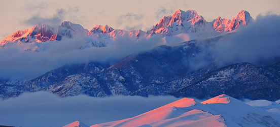 Snow covered mountains and dunes at sunset in Great Sand Dunes National Park and Preserve