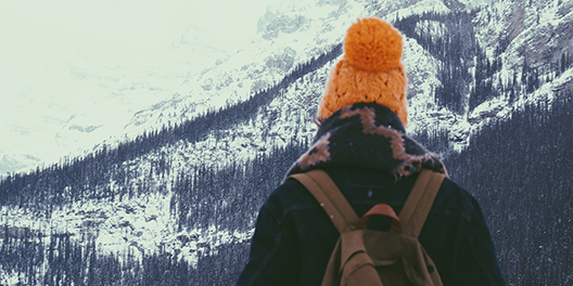 A person hiking in snowy mountains bundled in a scarf and orange hat