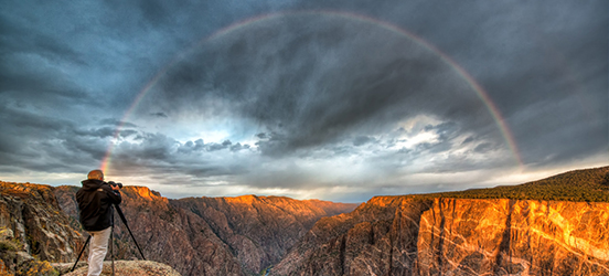 A photographer setting up a camera to capture a full rainbow covering the canyon