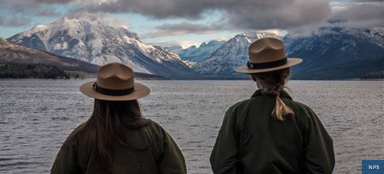 Two park rangers looking out at a body of water with snow covered mountains behind it