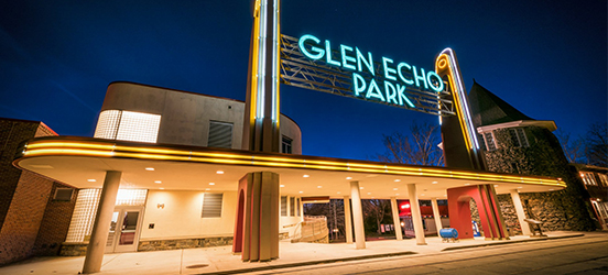 The outside of Glen Echo Park at night, glowing neon signs hgihlight the deco style