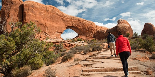Two people walking up steps on a hiking path in Arches National Park