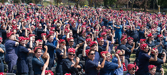 A large group of women dressed and posing like Rosie the Riveter