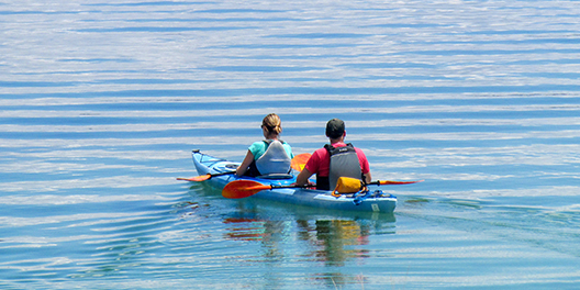 Two people in a blue kayak on a rippling lake in Yellowstone National Park