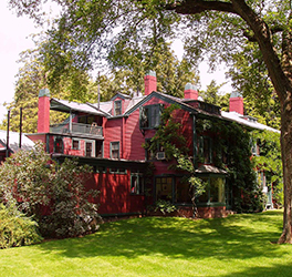 A large red building with black trim, vines climb up one side and behind it are lots of trees and bushes.