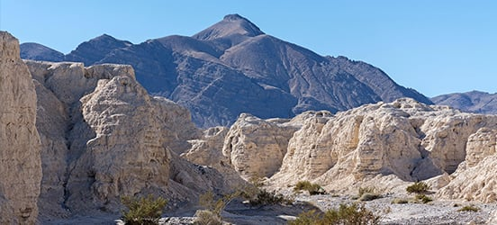 Desert landscape of Tule Springs Fossil Beds National Monument with beige colored rock steep rock formations and sandy brush in the foreground and larger mountians in the background
