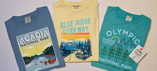 Three graphic Tshirts folded, showing their national park design