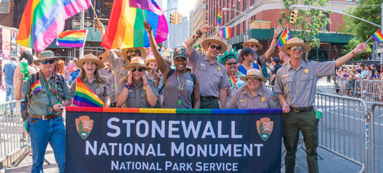 NPS Park Rangers carry a banner that says Stonewall National Monument in the NYC Pride Parade