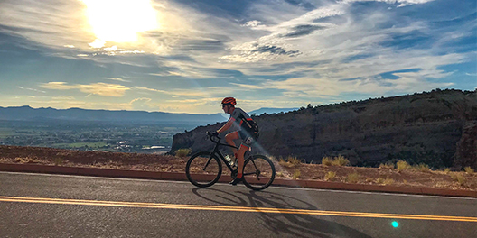 A person biking up a hill with mountains in the background at Colorado National Monument
