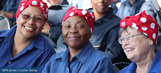 Three women smiling, dressed as Rosie the Riveter with denim button up shirts and red polka dotted bandanas around their head