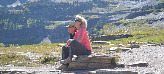 Russell James and Brenda Tanner sit on a large rock, looking out at the tree lined mountains around them