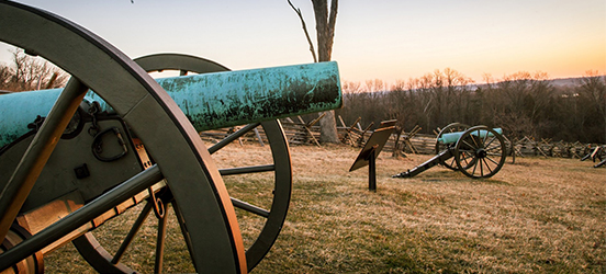 Cannons line a hill at sunset in Gettysburg National Military Park