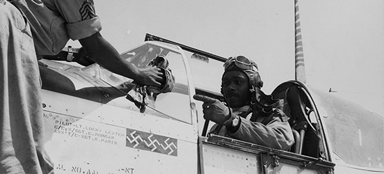 A historic image of an African-American airman sits in his World War II fighter plane wearing a leather helmet and googles