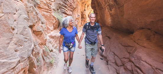 A couple holds hands and smiles while hiking in canyons in Zion National Park