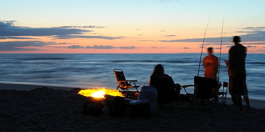 An image of a beach at Assateague Island National Seashore at sunset with a silhouette of three people sitting by a campfire