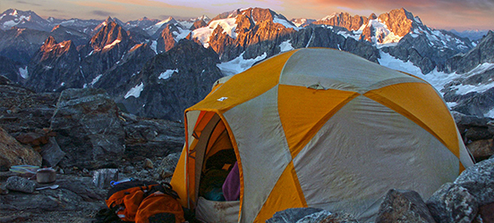 A tent pitched on rocky ground at a mountain top with other snow dusted mountains in the background at North Cascades National Park